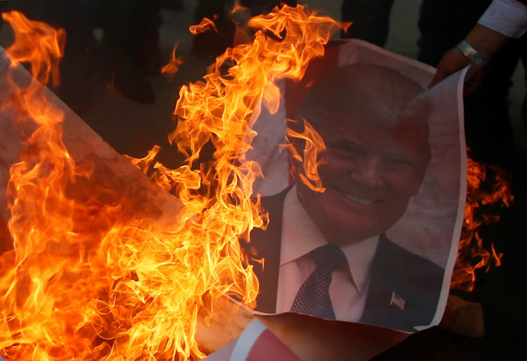 A Palestinian protester burns a poster depicting U.S. President Donald Trump during a protest against Trump's decision to recognize Jerusalem as the capital of Israel, in Gaza City December 7, 2017.