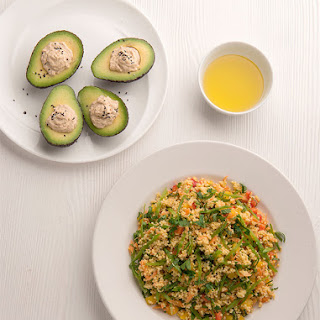 Warm Millet Salad And Avocado Stuffed With Hummus.
