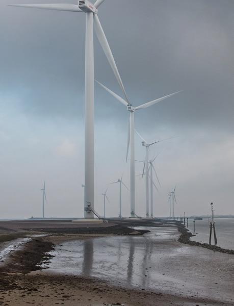 Wind turbines along a sandy shoreline