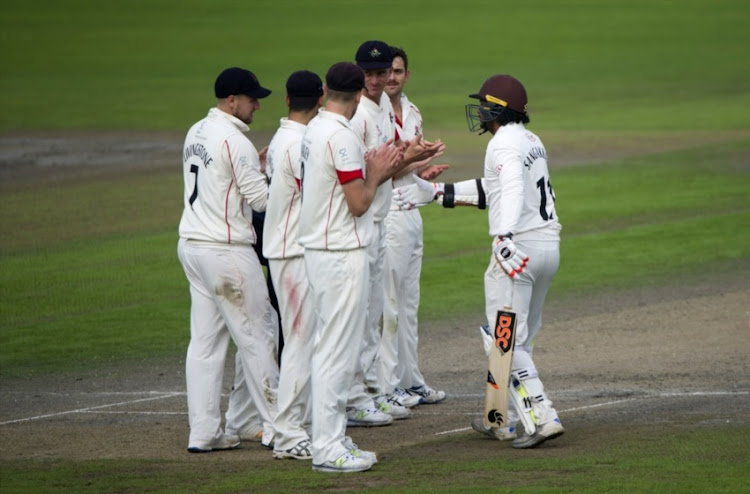Lancashire players clap Kumar Sangakkara of Surrey as he walks onto the pitch for the last time during the County Championship Division One match between Lancashire and Surrey at Old Trafford on September 27, 2017 in Manchester, England.