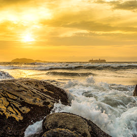 Sunrise with splash and ship, at Itaguaçú beach by Rqserra Henrique - Landscapes Waterscapes ( sunrise, rocks, ocean, beach, yellow, ship, clouds, water, splash, rqserra )