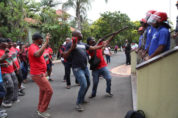 Striking Durban University of Technology staff protest outside the vice --chancellor's office in Durban as Mi7 security block access to the building on Thursday