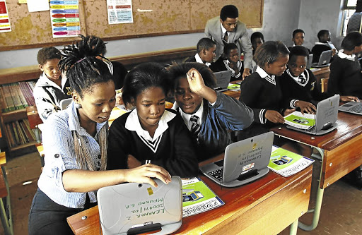 Unmet needs: Sinovuyo Apleni and Luthando Gubevu, founders of the Fundanii education project, teach computer skills to Mfundo Senior Primary pupils in Mdantsane. The education system produces a high number of social science graduates, who are not in high demand, compared with technical and service industry skills. Picture: Michael Pinyana