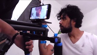 A photo of a movie being shot with an Android device and a device used to hold the camera steady. An arm holds the filming device while a young man appears in front of the camera.