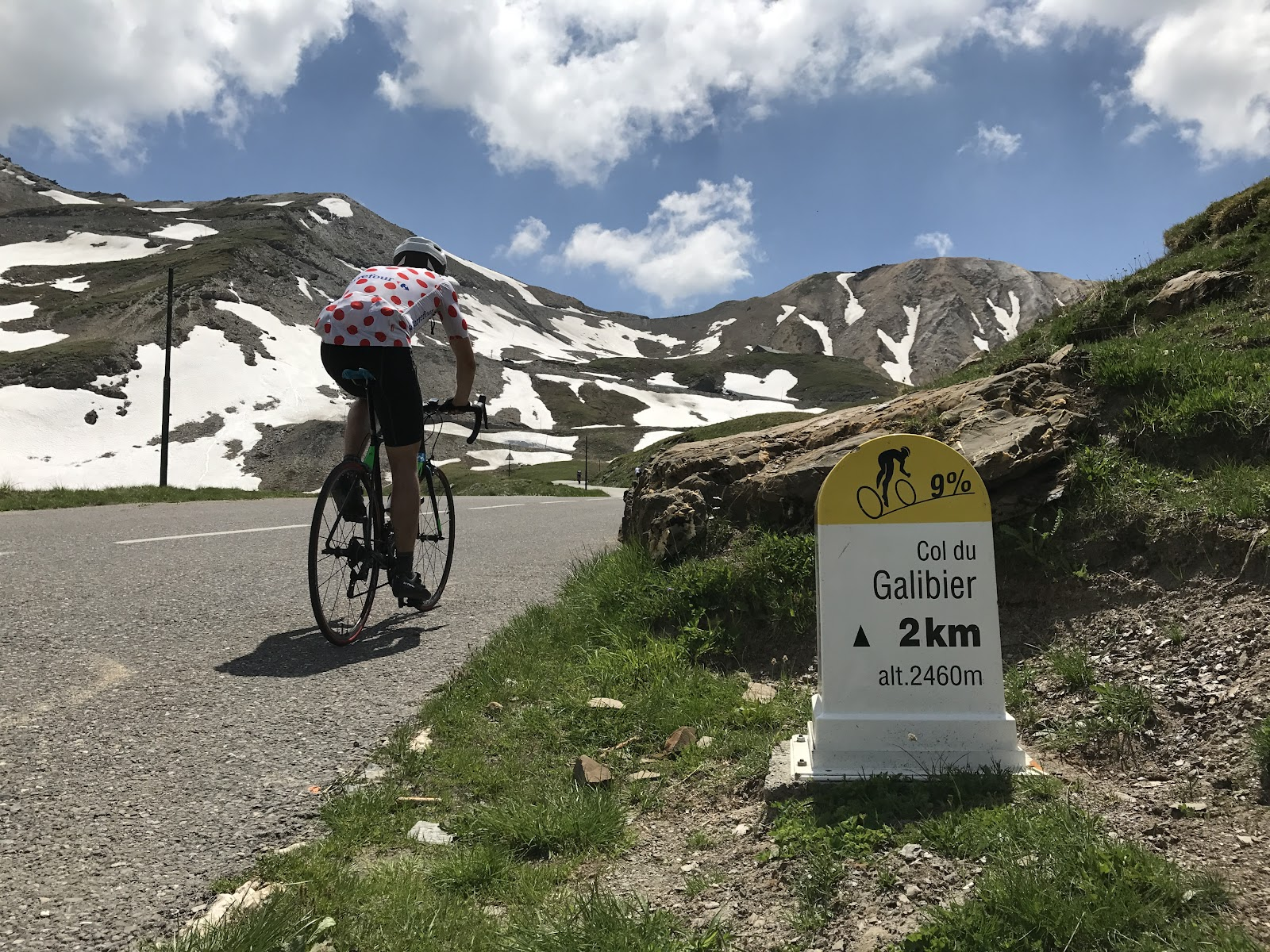 Cycling Col du Galibier - cyclist riding past the  2 km marker