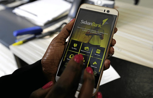 Banked: Mobile banking apps favour urban people with access to smartphones, such as this customer of Sidian Bank in the Kenyan bank's headquarters in Nairobi. Picture: REUTERS