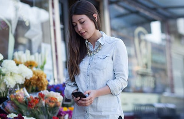 woman in denim shirt using a mobile phone