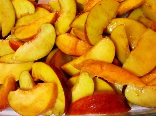 In a large bowl, toss together peaches, sugar, cinnamon, cardamom, vanilla and lemon juice;...