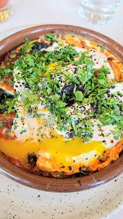 Brunch at Tusk in Portland, Tusk Brunch dish of Baked Eggs and Halloumi with spicy tomato, greens, yogurt, and sesame seeds