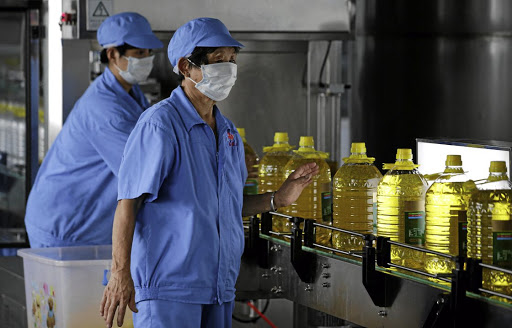 Bottles of soy oil made from soy beans imported from the US are seen on a production line at Liangyou Industry & Trade's factory in Qufu, Shandong province, China. Picture: REUTERS