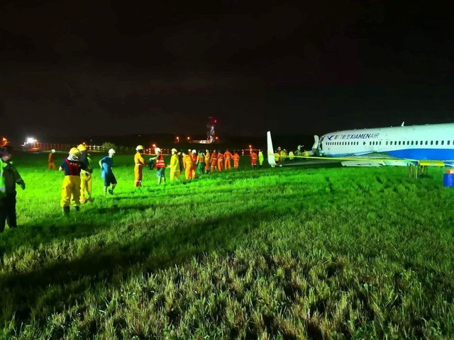 Rescuers gather near a Xiamen Airlines Boeing 737-800 on a grassy area next to airport perimeter fence after it overshot the runway at Ninoy Aquino International airport in Paranaque, Metro Manila in Philippines, early August 17, 2018.