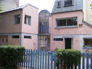 Photo: This pink stucco home has what appears to be a large stained glass window in the center section.