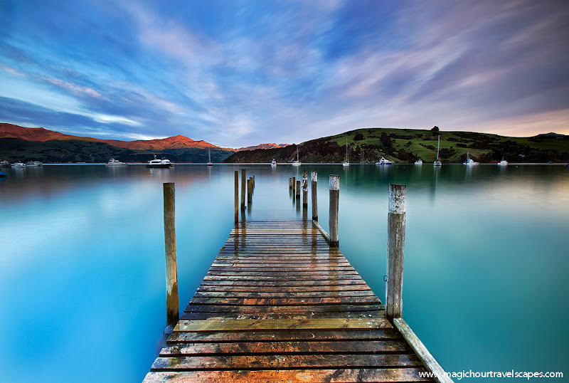 """Photo: Beautiful Akaroa on the Banks peninsula of New Zealand. Shot on assignment for Canon quite a few years back now. I used a 30 second exposure and GND filter to balance the sky and capture the radiating clouds. Details for next year's workshop """"South Island Escape"""" can be found on my blog. http://www.magichourunplugged.com/2012/09/22/new-zealand-workshop-2013-south-island-escape/"""