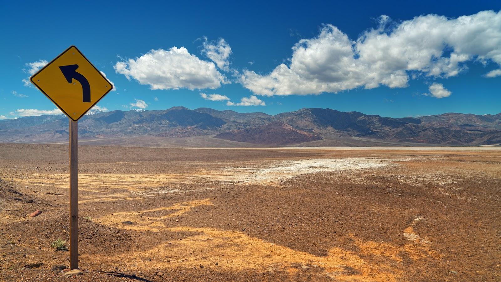נוף מדבר עם שלט המכווין שמאלה. שמיים כחולים
