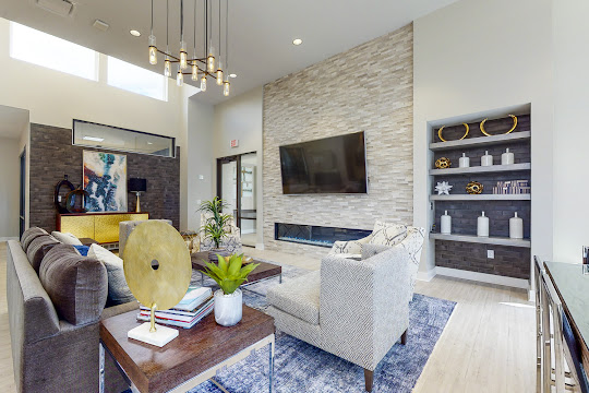 Community clubhouse with plush lounge seating, modern hanging light fixtures, and mounted TV above a fireplace