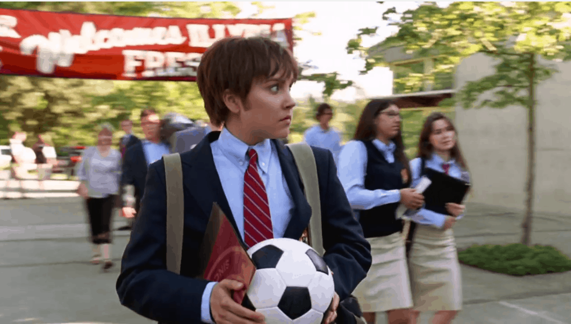 Amanda Bynes in She's the Man. Viola-as-Sebastian walks to school through a courtyard. He has short brown hair and wears boys' school uniform, a navy blazer and red striped tie. He holds a football in his hands, and looks around nervously.
