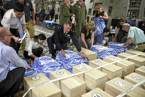 Crew and officials from the UN Command and the US Defense POW/MIA Accounting Agency (DPAA) secure UNC flags over transit cases of remains thought to be of US soldiers killed in the 1950-53 Korean War, before returning them to the US, in Wonsan, North Korea, on July 27 2018. Picture: US FORCES KOREA/HANDOUT VIA REUTERS