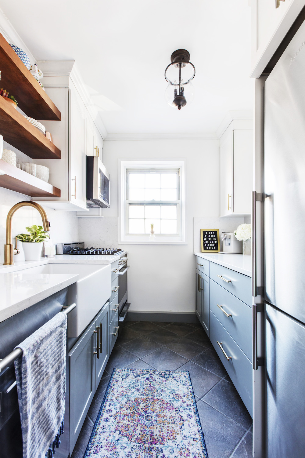 small apartment galley kitchen with two toned cabinets. blue cabinets are on bottom with white shaker upper cabinets. white countertops and white walls make the space feel bright and natural