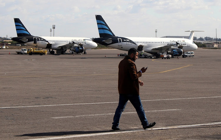 A man walks in front of Afriqiyah Airways planes parked at Tripoli International Airport in Libya on Friday.  Picture: REUTERS/HANI AMARA