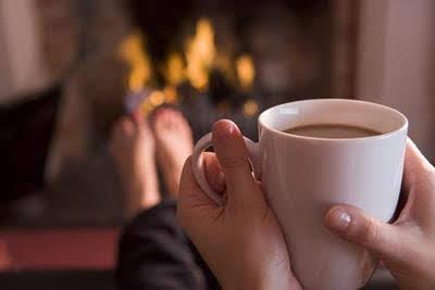 Taza de chocolate entre las manos y ante el fuego