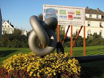 Kunstwerk: Symbolischer Knoten in CO-Pipeline. Transparent mit Stadtwappen, sowie Emblemen von PETO, Die Grünen, CDU, FDP, SPD, Die Linke: «Wir in Monheim am Rhein sin dgegen die CO-Pipeline! CO in diese Pipeline gehört verboten, drum machen wir hier einen Knoten! Initiative stoppt CO Pipeline».
