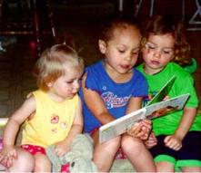 A child, who was formerly crying, being read to by another child