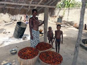 Photo: devant des paniers de fruit de palme qui, pilé, deviendra huile alimentaire très prisée