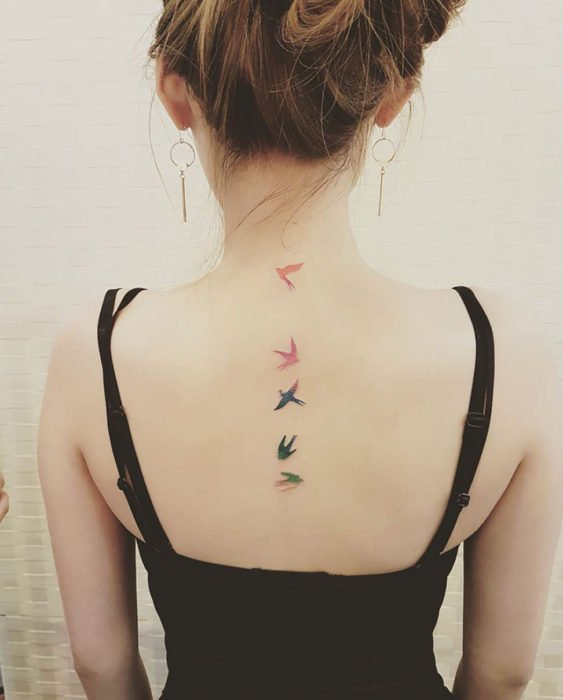 Tatuagens minimalistas de pássaros nas costas de uma garota