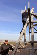 Photo: Glen, VE4GWN, holdling the ladder while Mark, VE4MAB, installs the mast mounting brackets