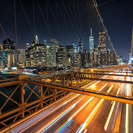 On the Bridge by Carol Ward - City,  Street & Park  Skylines ( brooklyn bridge, bridge view, light trails, manhattan, new york city, new york, bridge, nyc, brooklyn,  )