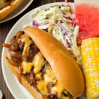 Brats with Caramelized Onions and Cheddar Cheese Sauce