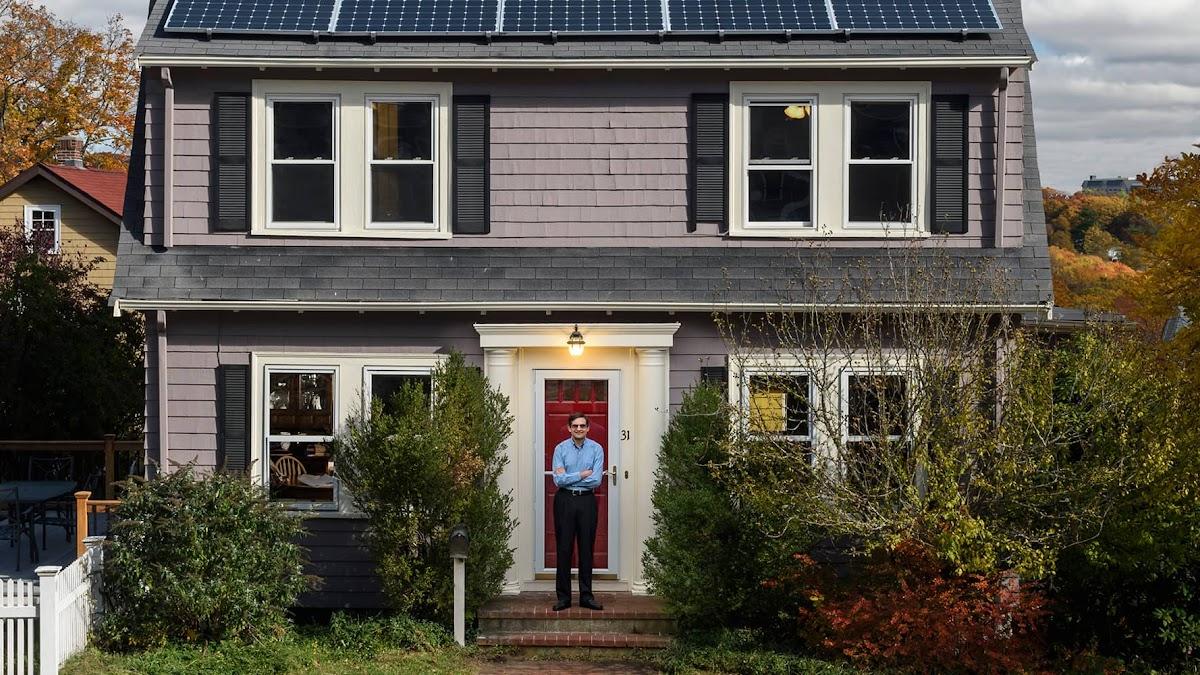 Un homme devant une maison pittoresque avec des panneaux solaires sur le toit