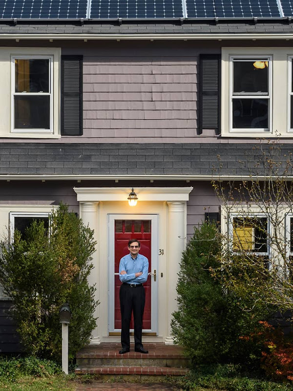 A man stands in front of a quaint home with solar panels on the roof.