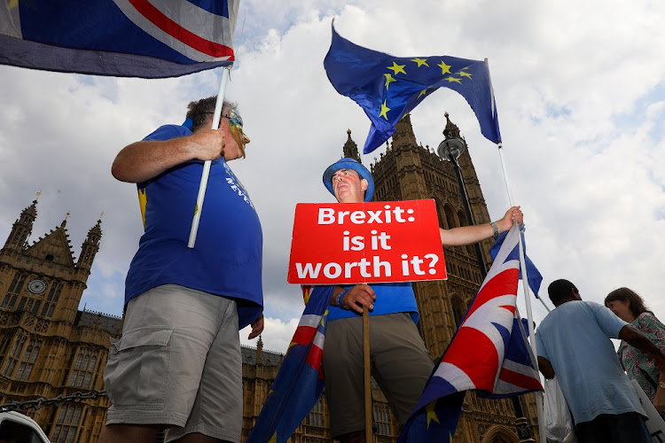 Demonstrators hold Union flags, also known as Union Jacks, and European Union flags during an anti-Brexit protest outside the Houses of Parliament in London, Britain, July 24 2018. Picture: BLOOMBERG