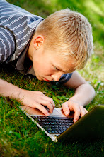 Photo: Young boy playing with a laptop on the grass outside