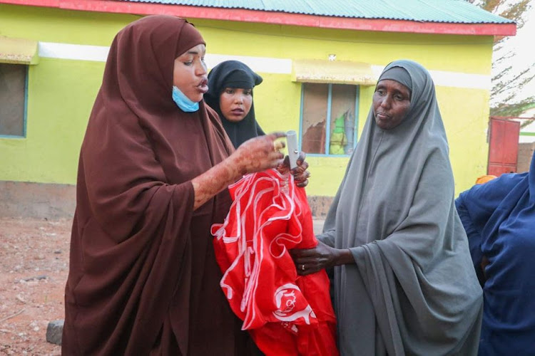 Garissa Woman Representative Anab Gure chats with women traders at the Garissa Livestock Market where she distributed umbrellas.