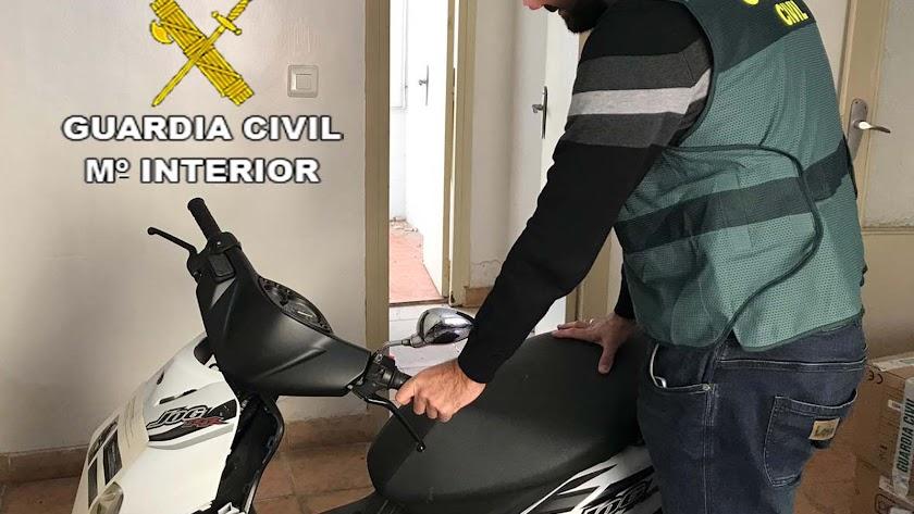 Agente junto a uno de los ciclomotores sustraídos.