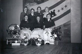 Photo: Het bestuur met het tafelkleed v.l.n.r. staand L. Doornbusch-Barels, G. Koers-Engbers, J. Martens-Vedder en R. Hofsteenge-Hadderingh. Zittend: G. Wilms-Boetting, W. Bruins-Leupen en J. Homan-Braams