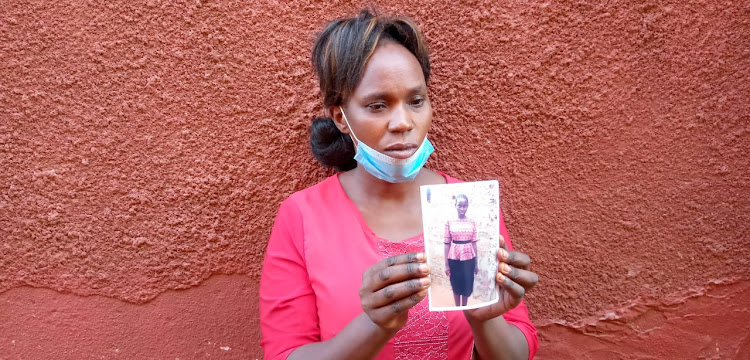 Felister Wangui, the mother, holds the photograph of her missing 13-year-old daughter Michelle Wangechi. The teenager went missing on Tuesday in Kalolenyi village in Voi sub-county and her whereabouts remain unknown.