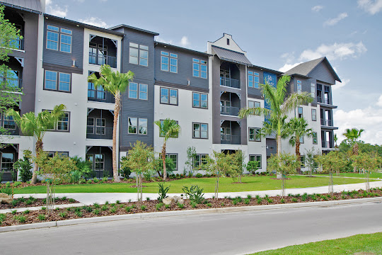 Apartment building with light gray siding and landscaping