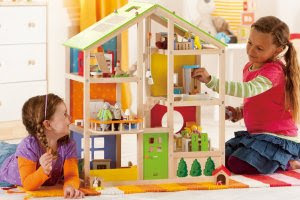 Two girls playing with wooden doll house