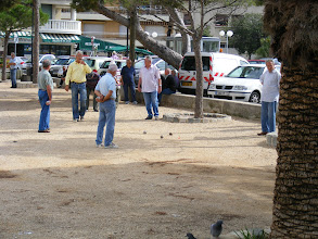 "Photo: And there are of course the ever present boules games – but here, it is more precisely pétanque. In boules, one may take a step (or even run) before throwing the ball. However, in pétanque, this is not permitted, and the game takes its name from the old Provençal phrase ""pès tancats,"" meaning ""feet anchored."""