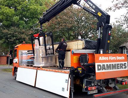 Załadunek elementów konstrukcyjnych na pomarańczowe auto ciężarowe