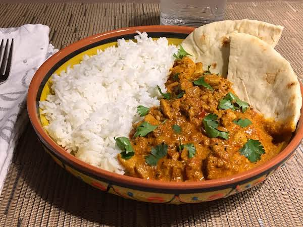 A Chicken Dish Served In A Bowl With Rice And Naan Bread.