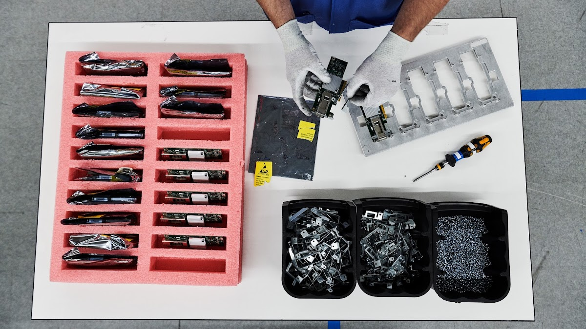 A technician assembles circuit boards and other components on a table full of organized parts