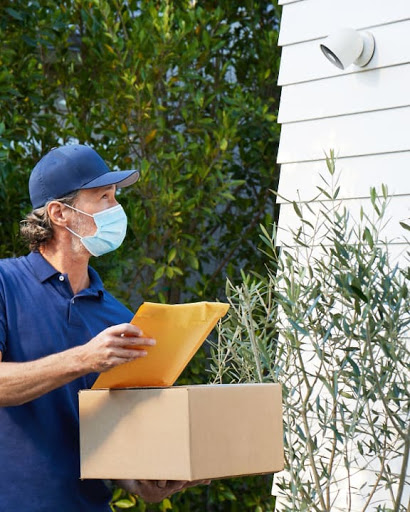 Nest Cam on the side of a home captures a deliveryman with a package.