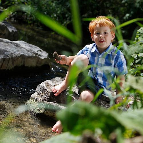 Ein kleiner Junge sitzt auf einem Stein am Bach und hält einen kleien Stein in der Hand
