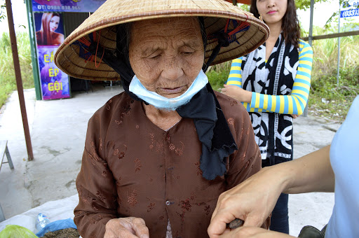 vietnam-woman-merchant.jpg - Wearing a typical hat to shield herself from the sun, this woman was determined to woo us to her wares.