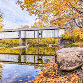 Covered Bridge Over Sugar Creek by Kenneth Keifer - Buildings & Architecture Bridges & Suspended Structures ( yesteryear, indiana, crossing, stream, old, reflection, wood, colorful, reflected, mirror image, leaves, landscape, rustic, historic, weathered, indiana covered bridges, mirror, national register of historic places, blue sky, nature, autumn, sunny, foliage, howe through truss, creek, montgomery county, darlington covered bridge, rocks, covered, clouds, vintage, midwest, white, still, scenic, sugar creek, rural, darlington, wooden, trees. leaves, covered bridge, fall, bridge, day, october, span )