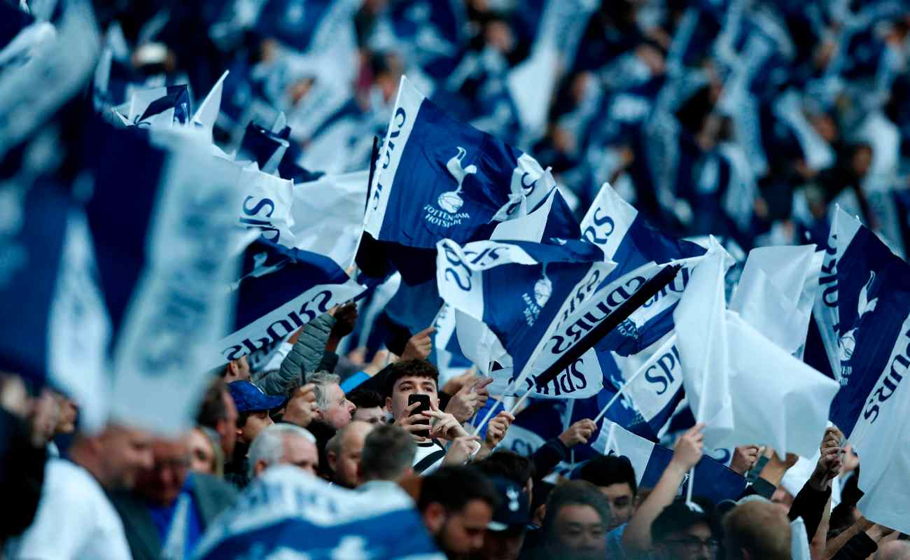 Tottenham Hotspur fans holding up flags in support of their team